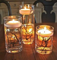 A couple of different sized glasses, water, some twigs or pine needles and floating candles