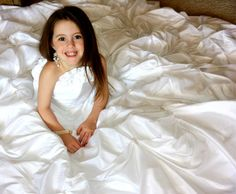 Photograph your flower girl in your wedding dress. Maybe she could display the photos at her own wedding!