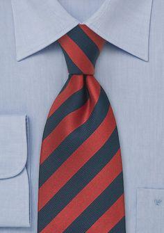 Cravate en soie avec élégantes rayures bleu marine et rouge intense. Soie 100%, 148 cm longue et 9 cm large.