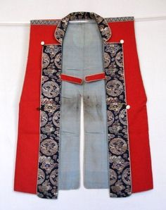 """Samurai's jinbaori which is worn over armor. The ground cloth is wool fabric called """"goro or goro fukuren"""" which had been imported from western countries such as England or Holland from 16th and 17th centuries. It has patchwork crest """"maru-ni-yaguruma mon"""" in the back. The front panels and the collar are made of silk brocade and the lining is plain silk. The design of the jinbaori was modeled on the clothing of the Spanish or the Portuguese who came to Japan around 16th century."""