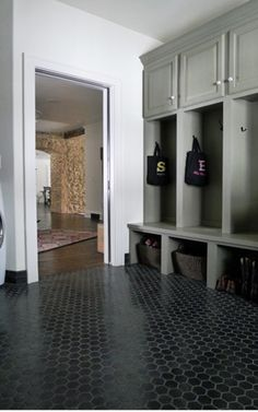 Big boot room concept, lush black hexagonal floor tiles and compartment storage for each persons coats, shoes etc