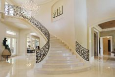 Dramatic scrolling staircase with crema marfil marble slab stairs,crystal chandelier,large art niche. Custom designed wrought iron railing. Double doors at landing on second level lead to outdoor patio. Venetian plaster walls throughout 1st floor.