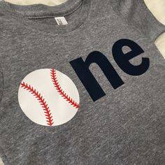 """This listing is for a baby boy first birthday shirt! The """"o"""" is a baseball to go with your little ones baseball birthday theme! All letters/numbers are professionally heat pressed onto a short sleeve"""