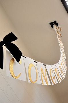 This Confetti Momma Graduation Banner is so irresistible. It can be such a chic party centerpiece for your graduation party. You could hang one on your mantle, drape one behind the snack table, or use it as a party photo prop!  This banner was designed using sophisticated glitter gold font, white card stock tiles, and embellished with luxurious black satin ribbon.  Size: 5.5 (height) x 63.75 (width)  Click here for more graduation decor: https://www.etsy.com/shop/ConfettiM...