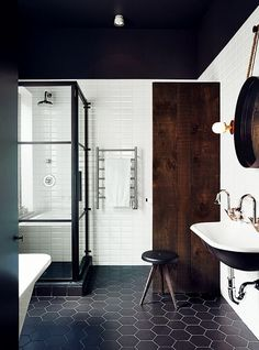 This Montreal bathroom was outfitted with oversize hexagonal floor tiles and a schoolhouse sink. The black painted ceiling gives the room a comforting feel by repeating the color of the floors.