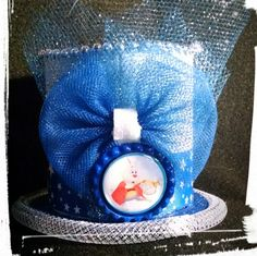 White rabbit inspired mini mad hatter hat. Glittery white and blue top hat embellished with silver beads, blue tulle bow and white rabbit bottle cap. | Shop this product here: http://spreesy.com/girlsjustwannahavfunbowtique/173 | Shop all of our products at http://spreesy.com/girlsjustwannahavfunbowtique    | Pinterest selling powered by Spreesy.com