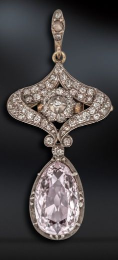 An Art Nouveau pink and white diamond pendant. The pear-shaped pink diamond weighs 2.77cts and suspends from a scroll mount set with graduated cushion-shaped diamonds. Fitted case by Paris of Liverpool.
