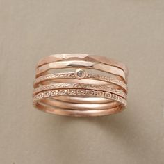 ROSARIA STACKING RINGS--A different texture assigned to each of Victoria Cunningham's five bands, one kissed with a dainty diamond. Handcrafted in USA of 14kt rose gold. Whole sizes 5 to 8. Set of 5