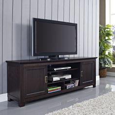 This modern 70-inch TV stand provides plenty of space for your electronic accessories and includes cut-outs to keep cords neat. The stand features sliding doors and a beautiful espresso finish, bringing a contemporary element of style to your home.