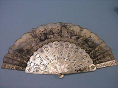 A 19th century Continental mother-of-pearl fan, guards pierced and gilded, sticks pierced, paper fan pierced and hand-painted with scenes of romantic dalliance, in original box