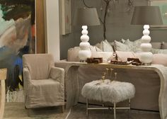 large colorful modern wall art; natural linen slipcovered chair; sleek curvy stone rectangular side table; industrial metal faux fur-topped footstool; delicate floral gold accent pieces; chunky-rustic wooden and metallic cross tabletop accessories; retro white ceramic table lamps with modern tan lampshades; natural ivory linen slipcovered sofa; modern ivory and tan funky piped throw pillows