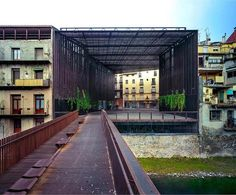 "Via thehardt La Lira, pedestrian bridge and public space by RCR Arquitecte located in Ripoll, Spain. After the demolition of ""la Lira"" theater in Ripoll, an urban void appears facing Ter river, on the city walls, from a street in the old town. This void is destined for a square, which does not want to lose the spirit of the theater. The project considers the irregular outline of the place, it occupies the space behind the wall overlooking the river, and covers everything with steel slats…"