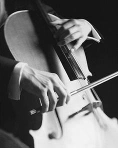 A nice black and white photo of a cellist playing.
