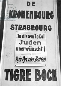 """Sign outside a pub forbidding entry to Jews, Strasbourg, Alsace, 1940. Sign reads: """"In our premises Jews unwanted! [This is a] Pure aryan establishment."""""""