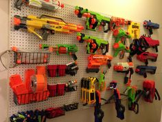 """The Armory"" A pegboard, long hooks, and a few baskets is a great way to organize your kid's nerf gun collection!"