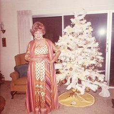 Elderly strawberry blonde widow in wild print ensemble and dangling earrings stands proudly in her sunbelt condominium next to elegant white flocked designer Christmas tree with gold tinsel and balls. 1970s vernacular photo snapshot-www.reservatory.net