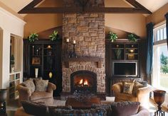 Stone fireplace in living room area with bookshelves on either slide