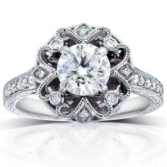 A round-cut moissanite gemstone graces the center of this stunning vintage-style engagement ring, crafted of 14-karat gold in your choice of color. The setting is studded by genuine, round-cut diamonds.