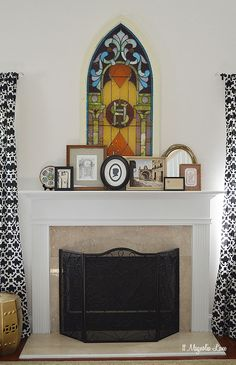 Two-story living and great rooms can be tricky to decorate.  Taller design elements look great and add height over a fireplace mantel.  This vintage stained glass window adds color, and a variety of framed pictures, artwork, and mirrors are propped in front and add visual interest. {Sponsored by HomeGoods}