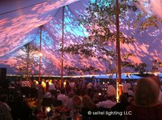 Leaf gobos uplight the tent in a pattern echoing the real trees decorating the tent poles