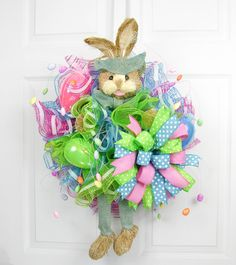 """A sweet sisal bunny with arms and legs worked into a combination of pink and blue striped deco mesh. Whispy egg picks with pink and green large eggs compliment the large Terri Bow. Measures 28""""H X 19"""""""
