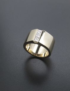 Wide gold band engagement ring with 3 small diamonds down the center.  Modern and simple!