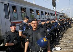 Human barrier: Croatian policemen line up as migrants look on from a packed train at the T...