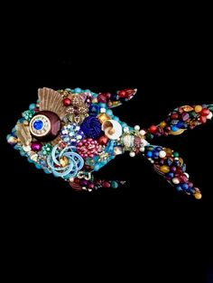 Angie Vintage Jewelry Tropical Fish Wall Art is hand- layered with vintage earrings, rhinestones, enamel, little sea shells, pins and more. What a beautiful vibrant wall hanging for your beach house or ocean themed room. Angie measures 9 x 5 inches and is made on a wood foundation