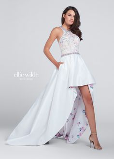 Get the exquisite look of Ellie Wilde EW117158 for your next formal occasion. Intricate beading and an embroidered floral design are found on the bodice of this gorgeous high-low style. The back features an open keyhole design and a gorgeous skirt that is short in the front and long in the back, with a fancy floral printed lining. This dress will wow the crowd at any event.