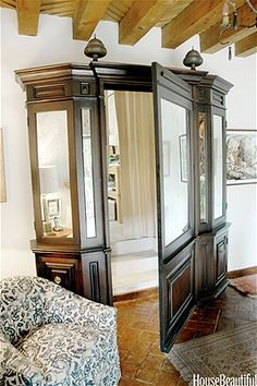 """""""My dream was to build a false armoire that would open to the garage and my studio. In the end, we built what looks like an armoire: the center panel is a secret passage with tall storage cabinets on either side.""""—Andrew Fisher, Interior Designer"""