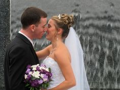 A newlywed kiss in front of Celebrations waterfall