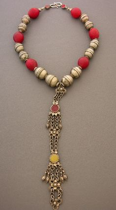 """A bold piece with a fascinating history. The highlight of this necklace is the  pendant, which was part of an Afghani headdress more than a century ago.  The beads in the necklace include six antique """"double"""" silver beads from  Afghanistan, six deep red antique Bohemian """"pigeon eggs,"""" and two  antique silver and red glass connectors near the """"S"""" shaped clasp."""