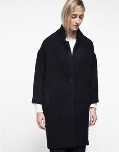 An elegant boucle coat from Studio Nicholson with a long, relaxed fit silhouette. Features dropped shoulders, open front, front pockets and single-button front closure.  	•	Textured boucle coat 	•	Dropped shoulders 	•	Open front 	•	Front pockets 	•