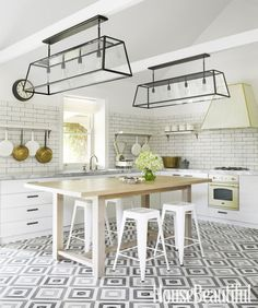 Designer Greg Natale hung pots from cantilevered shelves and chose Turkish terrazzo tiles to create a graphic floor in an all-white kitchen.