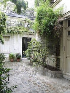 French courtyard with lush plants and shutters. European Farmhouse and French Country Decorating Style Photos. Outdoor Rooms, Outdoor Gardens, Roof Gardens, Small Gardens, Patio Design, Garden Design, Exterior Design, French Courtyard, Courtyard Entry