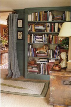 A green-painted built-in bookcase with fluted pediments, in an English country house style house.