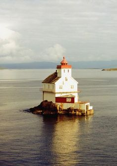 A lighthouse sits alone in a sea channel in Denmark.