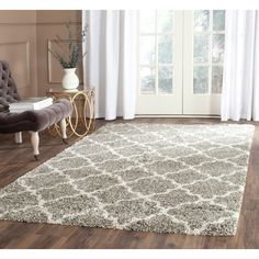 This Safavieh Hudson shag's design is a modern approach to the Moroccan quatrefoil style in neutral colors of grey and ivory, with grey as the primary background color. Crafted from polypropylene, thi