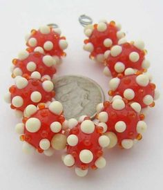 """Quantity: 9  Size: Approx. 8x13mm to 9x14mm (6mm = 1/4"""")  Hole Size: 1-1/2mm made on 1/16"""" mandrels  Colors: Lt. Ivory-Colored Glass & Tangerine Sparkle  Accent Beads: 10 - 4mm Lt. Beige Czech Glass Rounds    Gorgeous Tangerine Sparkle beads with Lt. Ivory & Tangerine Sparkle bumps for yummy, Summer jewelry designs. Kiln annealed, carefully cleaned & thoroughly inspected for your beading pleasure in beautiful West Tennessee. Colors may vary from monitor to monitor. Please contact us if you…"""