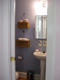 Nifty idea - using ribbons and small hooks to hang boxes, rather than installing bulky shelves.