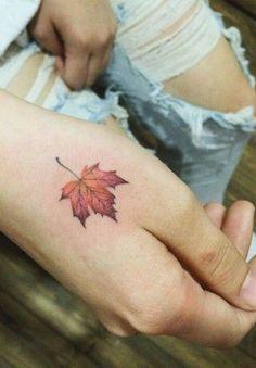 Tiny colorful maple leaf tattoo on hand