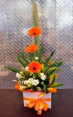 This floral arrangement would be the perfect gift for my wife. I love the orange flowers and matching bow in this arrangement. I wonder what other colors it comes in too! #Arreglosflorales