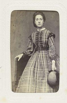 fdbb8a6c0a72f3 Studioportret van een jonge vrouw in een lange geruite jurk