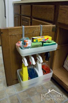 Kitchen Tour: Utilize the inside of your cabinet doors for storage. Bed Bath & Beyond, hang over the cabinet doors - baskets on the inside to store cleaning supplies etc. and a rod on the outside for hanging dish towels
