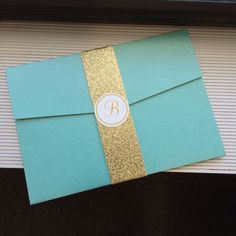 Wedding Invitation pocket shown in aqua blue accented with a gold glitter belly band.  For pricing contact info@theinviteonline.com