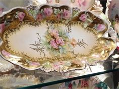 ITEM # 91644 (Box-5)   RS Prussia celery relish dish measuring 12 long by 6 wide, circa early 1900s.   This mold and floral decoration can be found in Mary Frank Gastons 4th series Collectors Encyclopedia of RS Prussia. RS Steeple mold 5 with clusters of small pink roses, gold enameled stems and heavy gold gilt border. RS Steeple mark #5.   Very good antique condition. Typical wear due to age and handling. The gold gilt and heavy boarder is amazing on this piece. Even the gold outlines on…