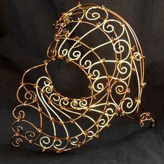 Stunning womens steampunk half face mask in bronze enamelled wire and brass wire. The mask features topaz colour glass seed beads. (Pic from Etsy)
