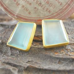 These stunning handmade geometric stud earrings feature beautiful faceted semi-precious Aqua Chalcedony stones encased in a brushed 18k gold plated sterling silver setting. #Embersjewellery #Jewellery#accessories #giftforher #Aquachalcedony