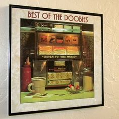 This is an actual vintage album cover containing the original vinyl record album. It has been mounted in a black plastic frame with a glass front and is ready for you to hang on your wall.   Framed Vintage Record Album Cover – Best of the Doobies