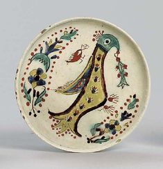 A KUTAHYA POTTERY SAUCER DISHOttoman Turkish 18th centuryOf shallow rounded form with vertical rim on short foot, the white interior painted in bright colours with the figure of a stylised peacock holding a stylised leaf in its beak, stylised floral sprays above and below, a simple blue line around the rim, rim chips, foot drilled Ceramic Plates, Ceramic Pottery, Turkish Tiles, Pottery Designs, Ceramic Design, Blue Line, Interior Paint, Islamic Art, Earthenware